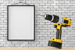 Yellow Rechargeable and Cordless Drill in front of Brick Wall wi Royalty Free Stock Photos