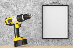 Yellow Rechargeable and Cordless Drill in front of Concrete Wall Stock Photography