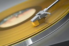 Yellow record on turntable. Tilted close up of headshell and stylus on a turntable with yellow vinyl record stock image