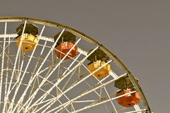 Yellow and red. Carriages take a break mid air on the big wheel Stock Photo