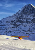 Yellow red airplane landing at the mountain airfield in swiss al Stock Image