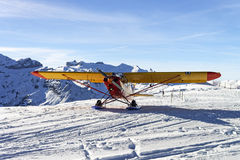 Yellow red airplane at the mountain airfield in swiss alps Stock Photos