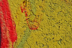 Yellow and red background. Rough concrete wall covered by yellow and red peeling paint Stock Photography