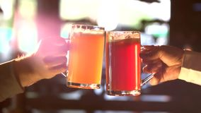 Yellow and red beer clinking, slow-mo. Two men hands clinkings with mugs of different beer stock video footage