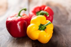 Yellow and red bell peppers. On wooden background, fresh vegetables Royalty Free Stock Photos