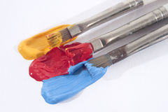 Yellow Red and Blue Acrylic Paints and Paintbrushes Stock Images