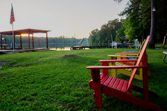 Yellow red blue chairs at the lake. Sit and watch the sunset relaxed royalty free stock photography