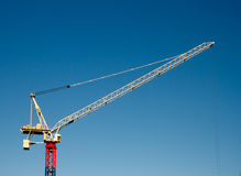 Yellow red and blue hoisting crane. Against clear blue sky.  Kings cross, England Royalty Free Stock Photography
