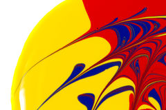 Yellow, red, and blue paint swirls on a white back. Abstract image of yellow, red, and blue paint swirls on a white background stock image