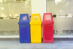 Yellow, red and blue recycling bin on the floor Stock Photos