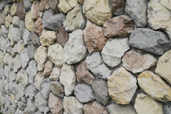 Yellow, red, blue, stones and pebbles on gray wall, background Stock Photography