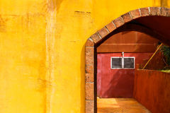 Yellow and Red Building. Abstract yellow and red building with arch and window stock image
