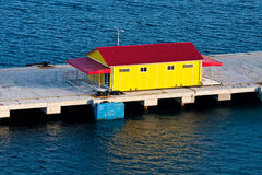 Yellow and Red Building on Pier Over Blue Water Stock Images