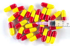 Yellow with red capsules and syringe, medication cure Royalty Free Stock Images