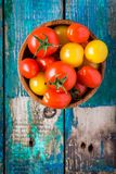 Yellow and red cherry tomatoes in a bowl on rustic wooden table Stock Images