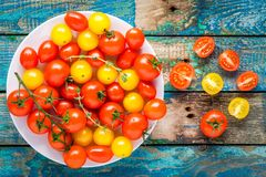 Yellow and red cherry tomatoes in a bowl on rustic wooden table Royalty Free Stock Image