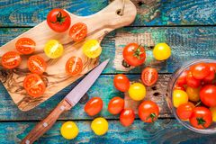 Yellow and red cherry tomatoes cuted on a cutting board Royalty Free Stock Images