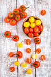 Yellow and red cherry tomatoes on old white wooden table Stock Image