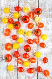 Yellow and red cherry tomatoes on old white wooden table Stock Photo