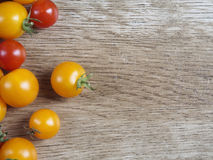 Yellow and red cherry tomatoes on wood background Stock Photography