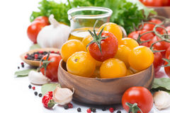 Yellow and red cherry tomatoes in wooden bowl, olive oil, herbs Stock Image