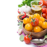 Yellow and red cherry tomatoes in wooden bowl, olive oil Royalty Free Stock Images