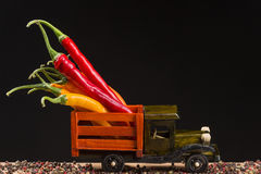 Yellow and red chili pepper in the back of a wooden truck. Yellow and red chili peppers in the back of a wooden lorry on an old wooden board Stock Images