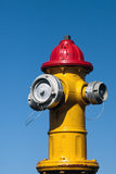Yellow and red fire hydrant. Against a blue sky royalty free stock image