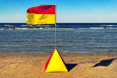 Yellow-red flag on the beach of the Baltic Sea in the summer. Latvia. Yellow-red flag on a yellow sandy beaches of the Baltic Sea in the summer sunny day on a Stock Images