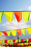 Yellow and red flags. Blue sky background. Stock Photos