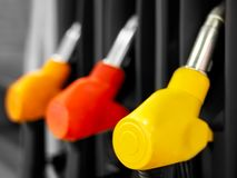 Yellow red fuel pistols on fuel station Stock Photography