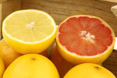 Yellow and red grapefruit and a cut one Royalty Free Stock Photography