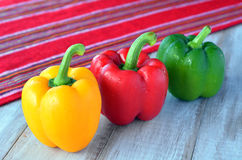 Yellow, red and green capsicum on a wooden table Royalty Free Stock Photography