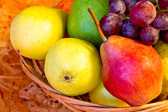 Yellow, red and green pears with red grapes. In woven basket on wooden table Stock Images