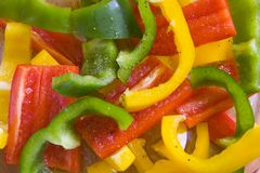 Yellow, red and green sliced peppers. Dressed with olive oil and ground pepper in glass bowl Stock Images