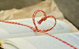 Yellow and Red Heart Knot on Black Labeled Book Royalty Free Stock Photo
