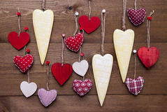 Yellow and Red Hearts For Valentines Daecoration. Many Yellow And Red Hearts Hanging Infront Of Wooden Background. Romantic Decoration For Valentines Day. Rustic royalty free stock images