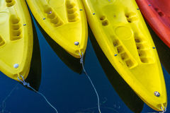 Yellow and red kayaks on blue water Royalty Free Stock Images