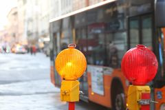 Yellow and red lamps in roadworks in the city with a bus Stock Photography