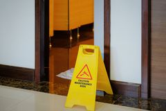 Yellow and red maintenance in progress warning sign in front of. Open door into a bathroom restroom with vintage traditional wooden door stock photo