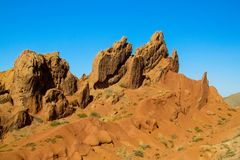 Yellow and red mountains and rock formation valley. Skazka fairy tale canyon in Kirgyzstan, in Kyrgyz Republic, near Issuk Kul lake. Red yellow castle shaped stock photo