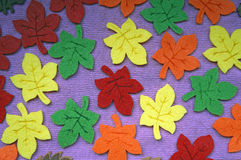Yellow, red, orange and green Maple leaves out of felt on fabric Royalty Free Stock Photography