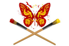 Yellow and red painted butterfly hover above two paintbrushes Royalty Free Stock Images
