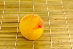 Yellow red peach whole juicy ripe fruit on a natural base light beige with vertical stripes royalty free stock photos