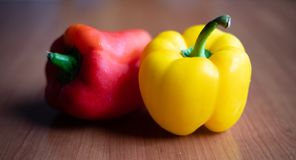 Yellow and red peppers on wooden table at home stock image