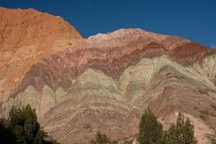Rainbow mountains in Purmamarca Argentina with hikers royalty free stock photo