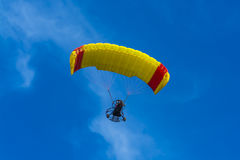 Yellow and red powered tandem para glider flying Royalty Free Stock Images