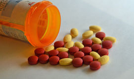 Yellow and red prescription drugs by a pill bottle Stock Images