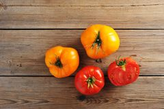 Yellow and red raw ripe whole tomatoes rustic wooden background. Top view Royalty Free Stock Image