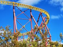 A yellow and red roller coaster track against a deep blue sky. royalty free stock images